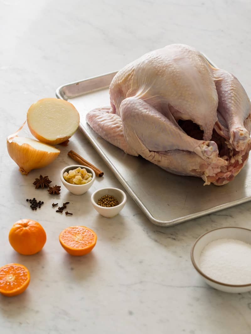 Ingredients for citrus and herb roasted turkey on a marble countertop.