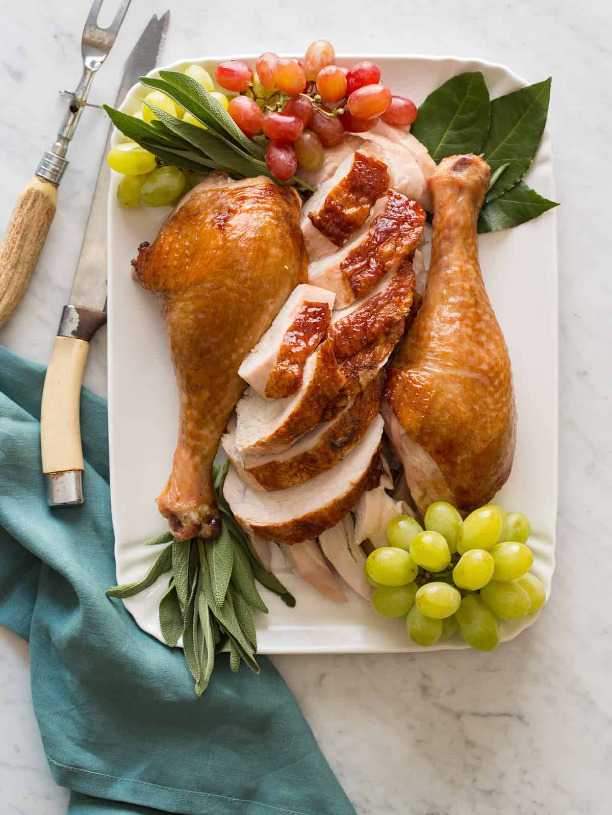 A platter of citrus and herb roasted turkey garnished with grapes and herbs with carving utensils.
