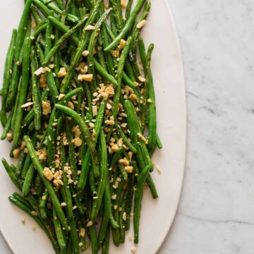 A platter of lightly roasted green beans with parmesan almond crumble.