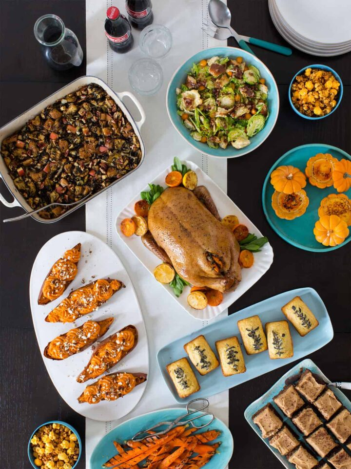 A table top view of platters and serving bowls full of non traditional Thanksgiving recipes.
