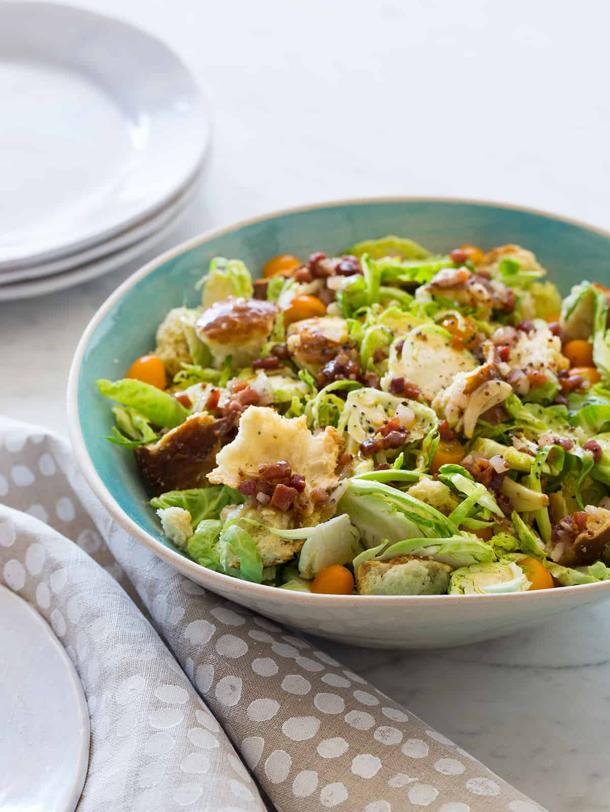A bowl of shaved Brussels sprouts salad with a warm prosciutto mustard vinaigrette.