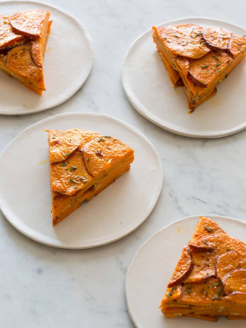Sweet potato and rosemary gratin slices on plates.