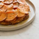 A close up of sweet potato and rosemary gratin on a plate.