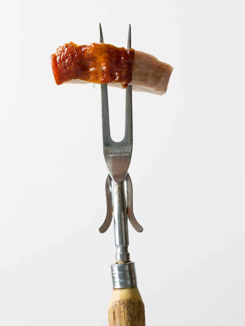 A close up of a piece of citrus and herb roasted turkey on a carving fork.