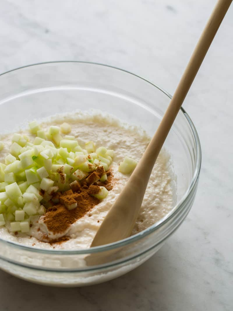 A bowl of apple cinnamon pancake batter ingredients with a wooden spoon.