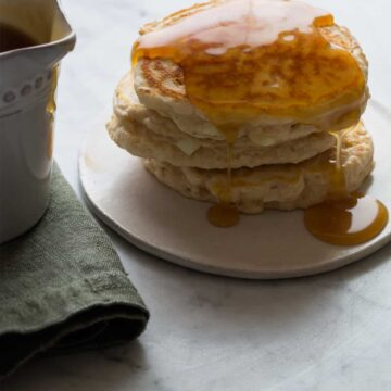 A close up of apple cinnamon pancakes with brown sugar buttermilk syrup.