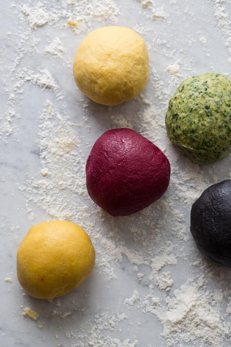 A close up of a variety of colorful pasta dough balls.