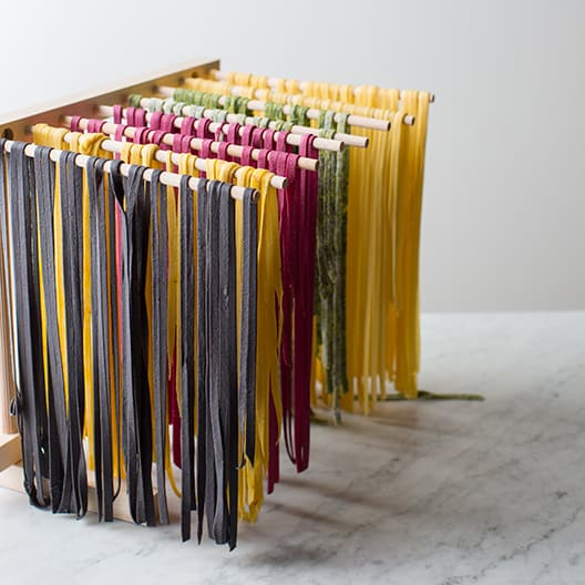 Multicolored homemade pasta hanging on pasta drying rack.