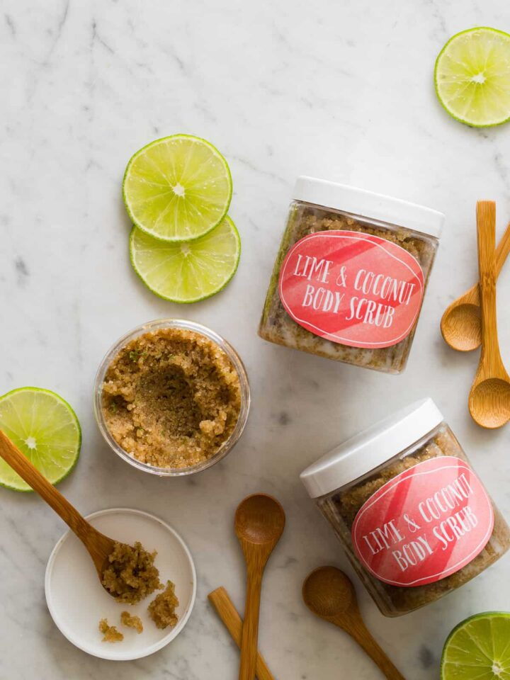 Lime and coconut body scrub in labeled containers with lime wheels and wooden spoons.