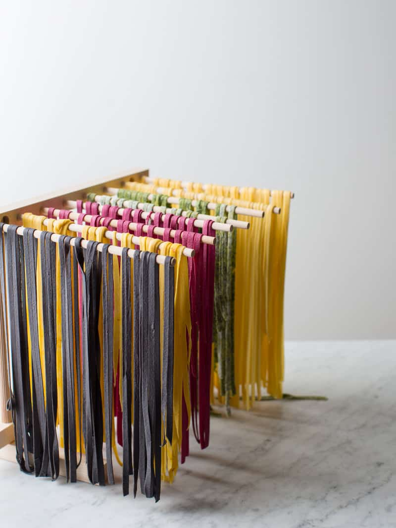 A variety of colorful pasta drying on a pasta rack.