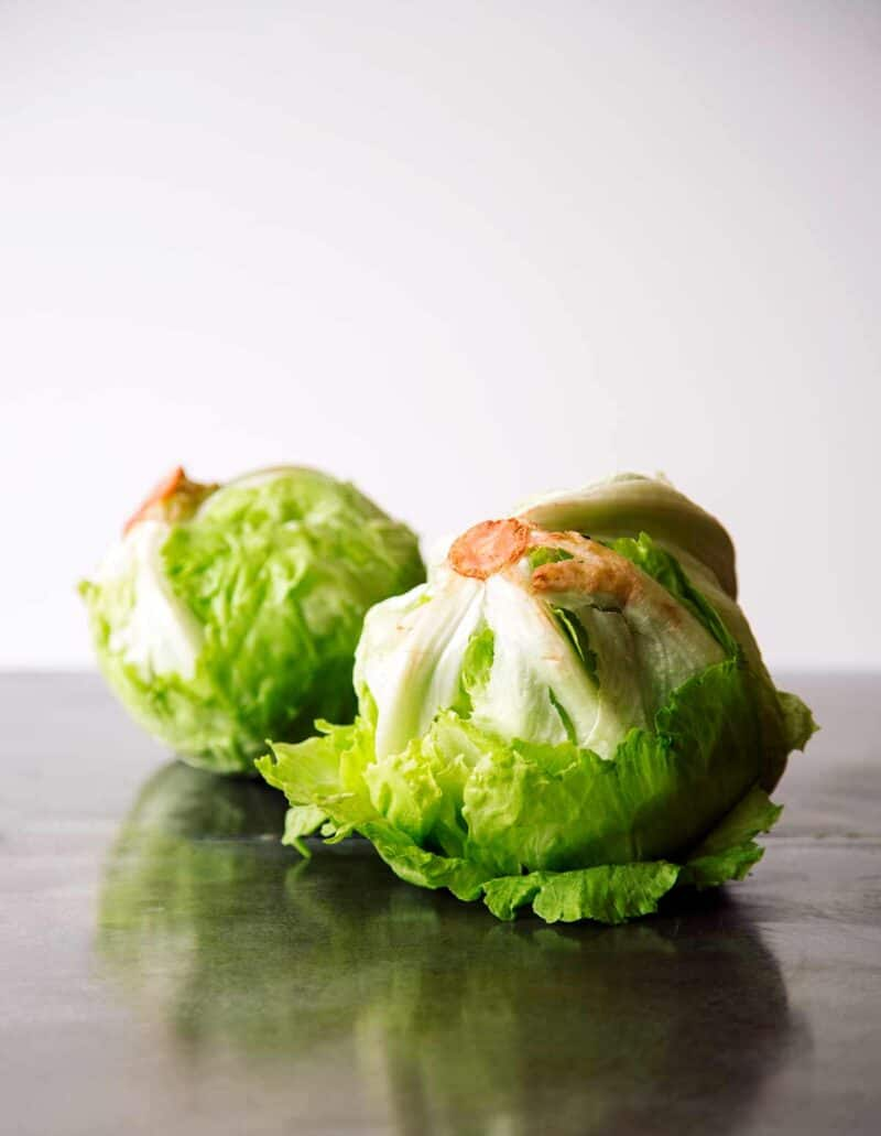 A close up of two heads of iceberg lettuce.