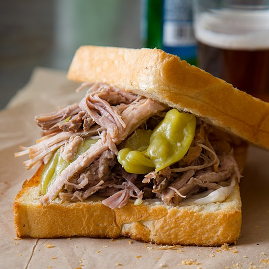 A close up of a slightly opened slow cooker pickled pulled pork sandwich.