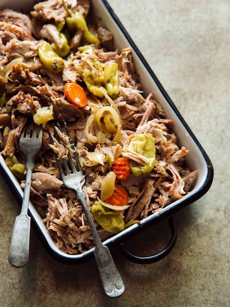 A dish is filled with slow cooker pickled pulled pork with forks.