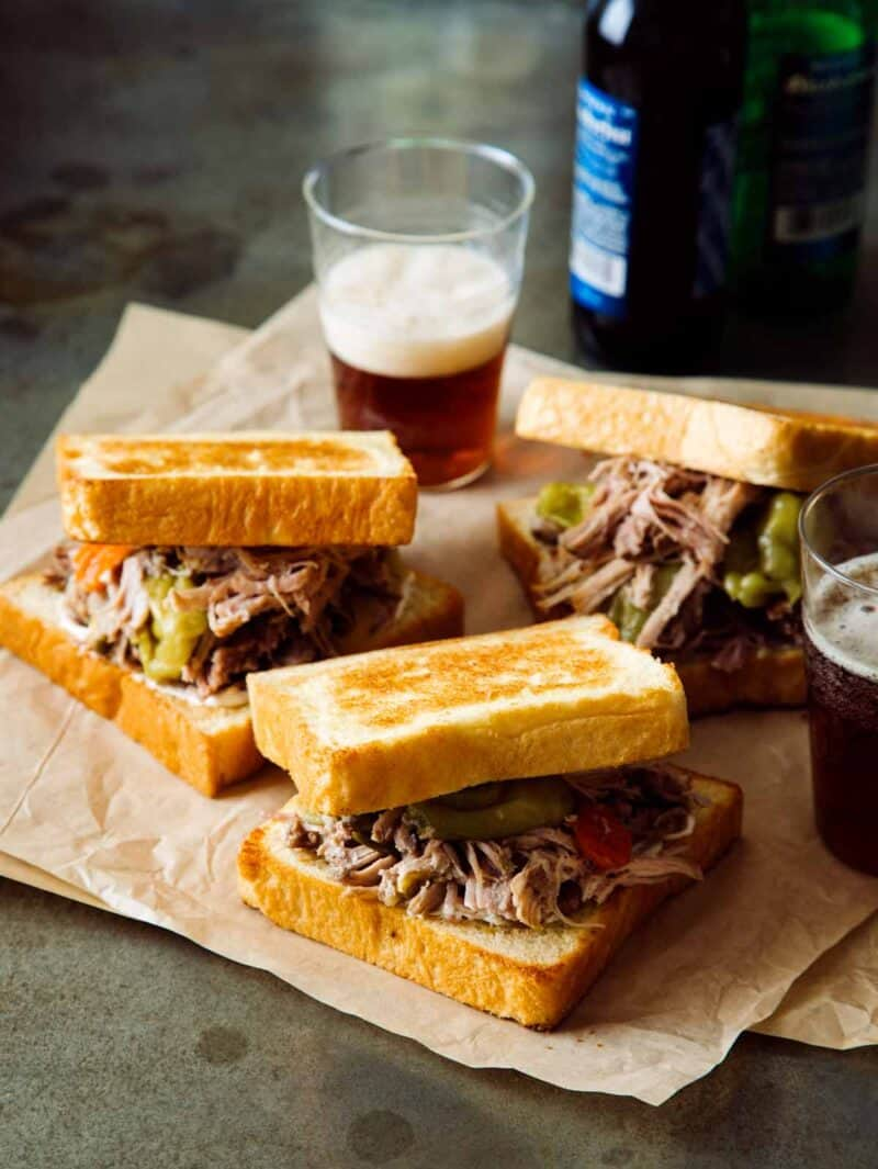 Slow cooker pickled pulled pork sandwiches with a beer in the background.