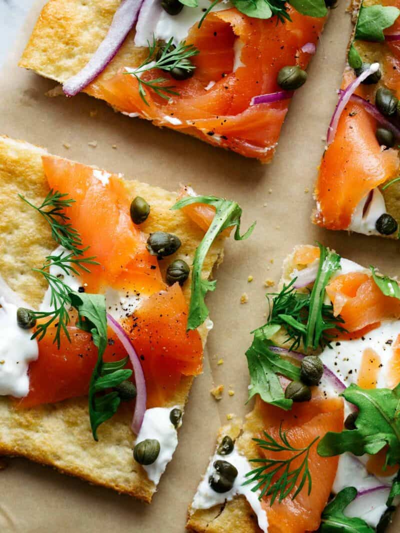 A close up of sliced smoked salmon pizza.