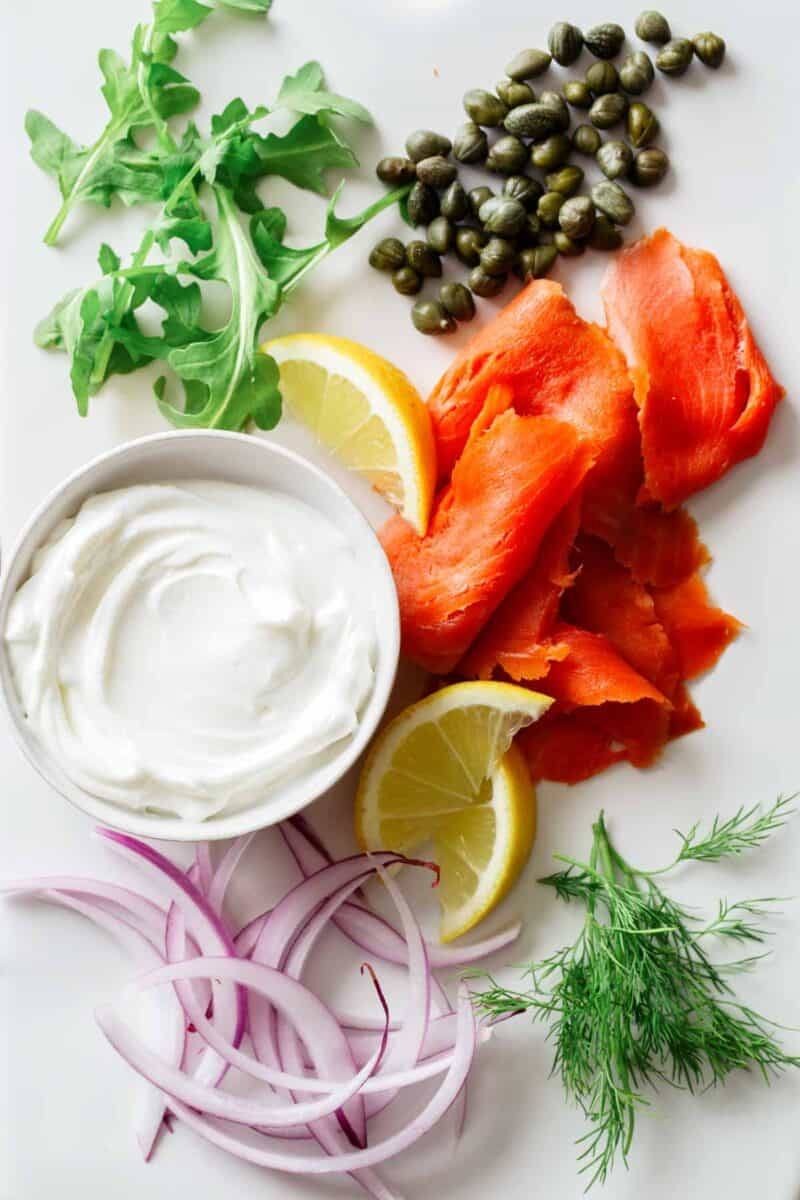 A close up of ingredients for smoked salmon pizza.