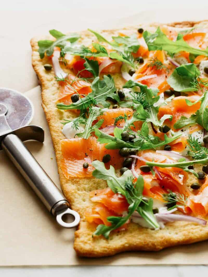 A close up of smoked salmon pizza with a pizza cutting wheel.