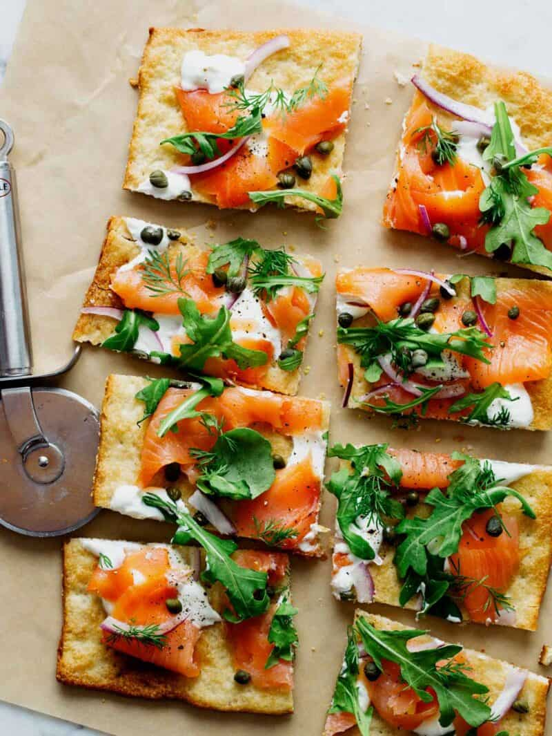 A sliced smoked salmon pizza with a pizza cutting wheel.