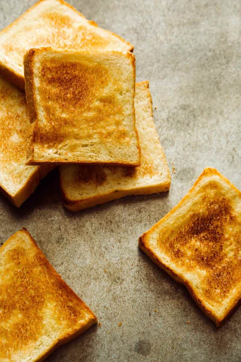 Several pieces of toasted white bread.