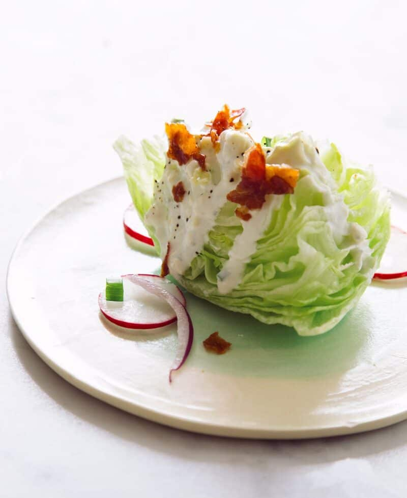 A wedge salad on a white plate.