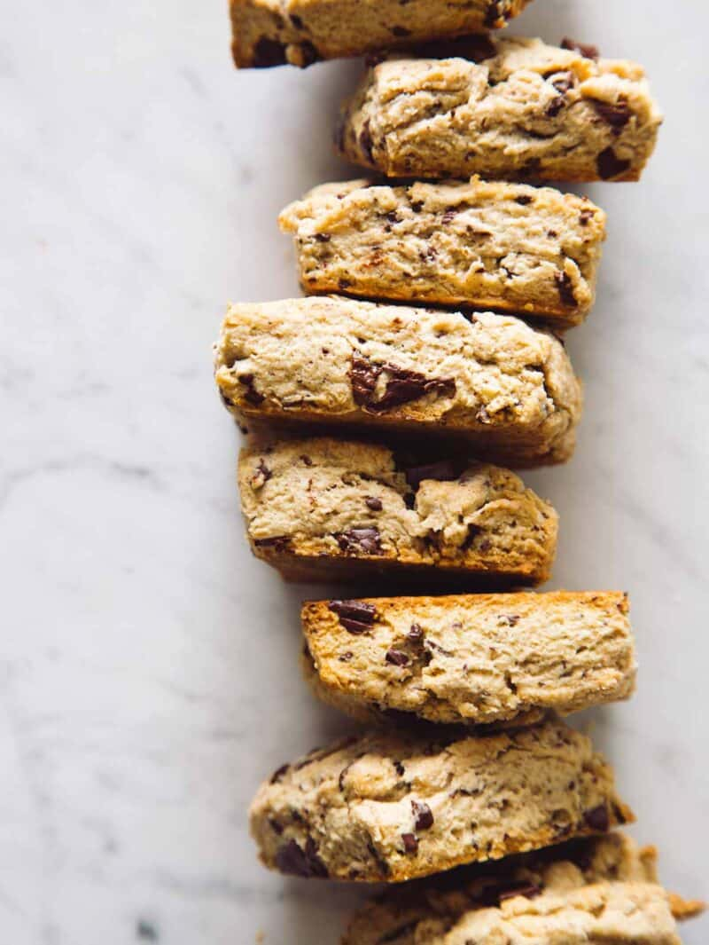 A close up of stacked chocolate chunk and cinnamon scones.