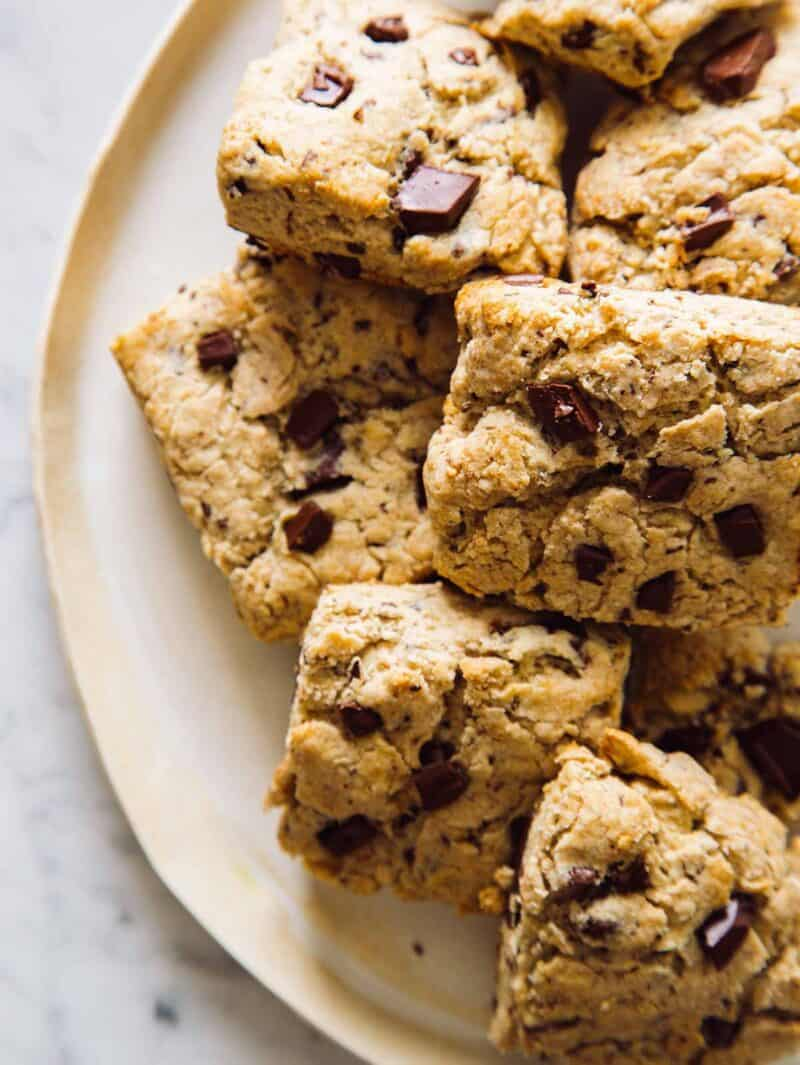 A plate full of chocolate chunk and cinnamon scones.