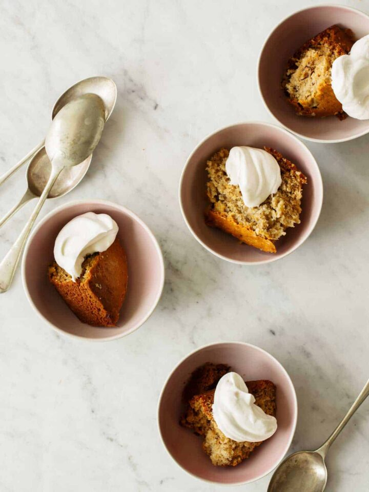 Bowls of chai banana cake with dollops of whipped cream and spoons on the side.