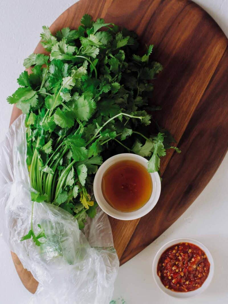 A bunch of cilantro and bowls of wet ingredients on a wooden cutting board.