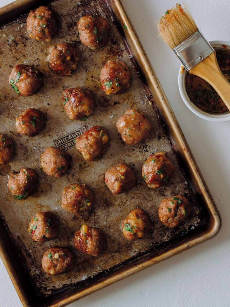 A sheet pan of finished ginger garlic cocktail meatballs with a bowl of glaze and brush.