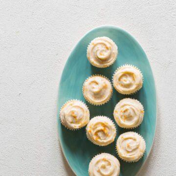 A green platter of butter cupcakes with grapefruit buttercream.