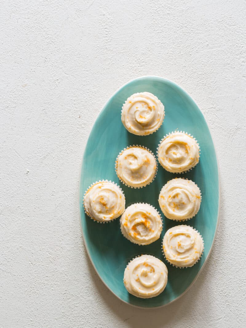 A plate of butter cupcakes with grapefruit buttercream frosting and grapefruit zest.