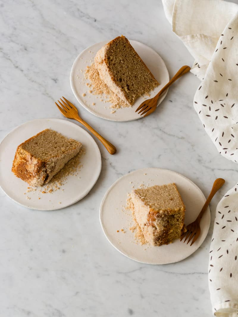 Cinnamon sour cream cake slices on plates with a linen next to it.