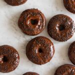 Baked chocolate doughnuts with chocolate frosting and sprinkles.