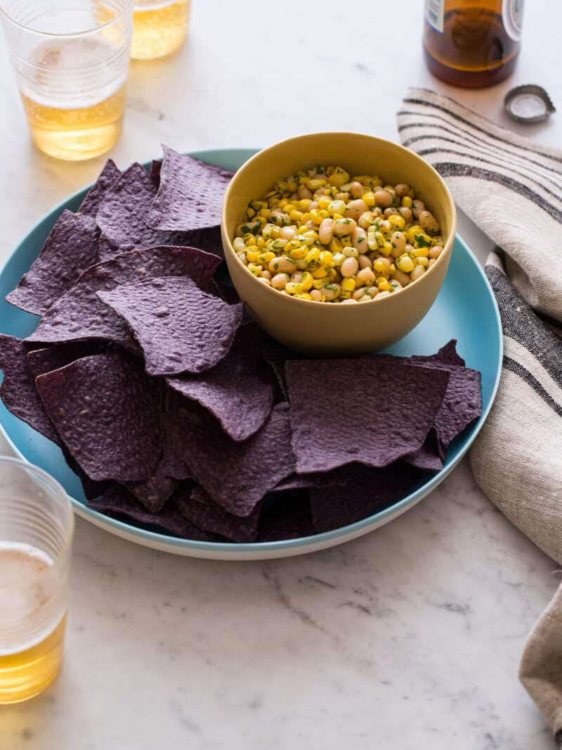 A plate of blue corn tortilla chips with a bowl of white bean and corn salsa.