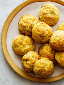 A close up of havarti and green onion cornmeal drop biscuits on a plate.