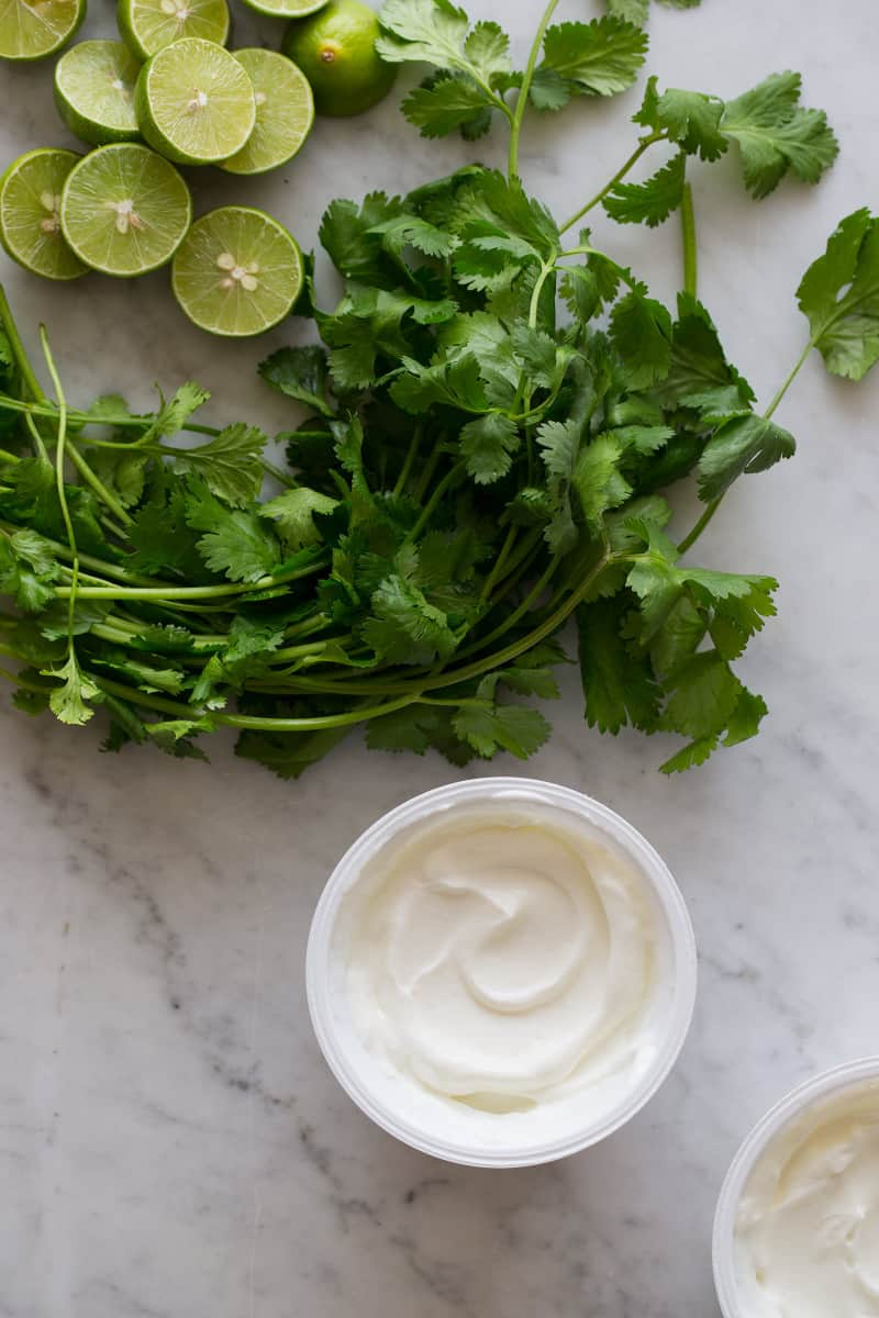 A close up of key lime halves, cilantro, and yogurt.