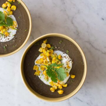 Bowls of spicy black bean soup garnished with sour cream, roasted corn, and cilantro.