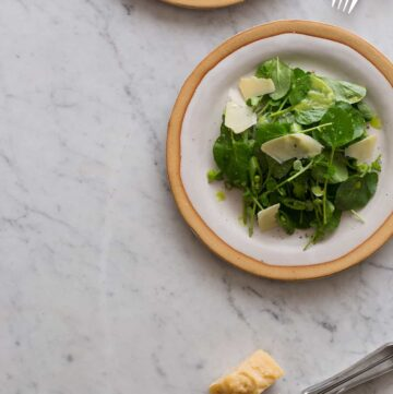 Watercress salad with green apple vinaigrette on a plate.