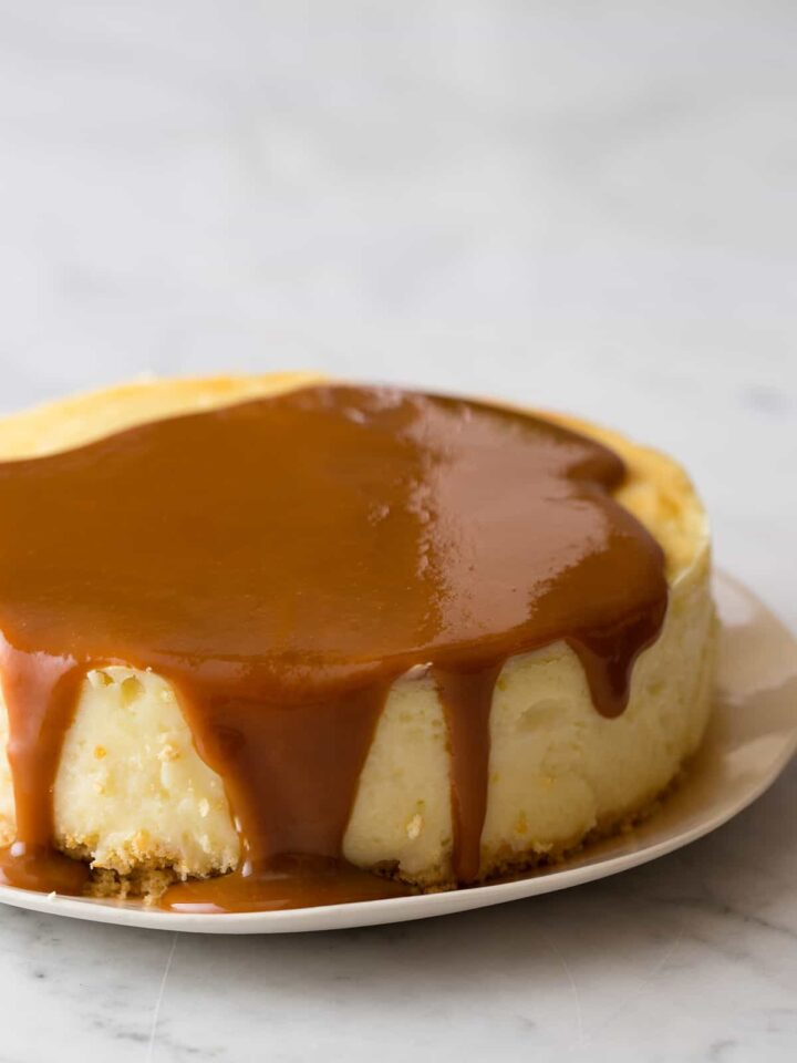 A close up of New York style cheesecake with cajeta drizzled on top.