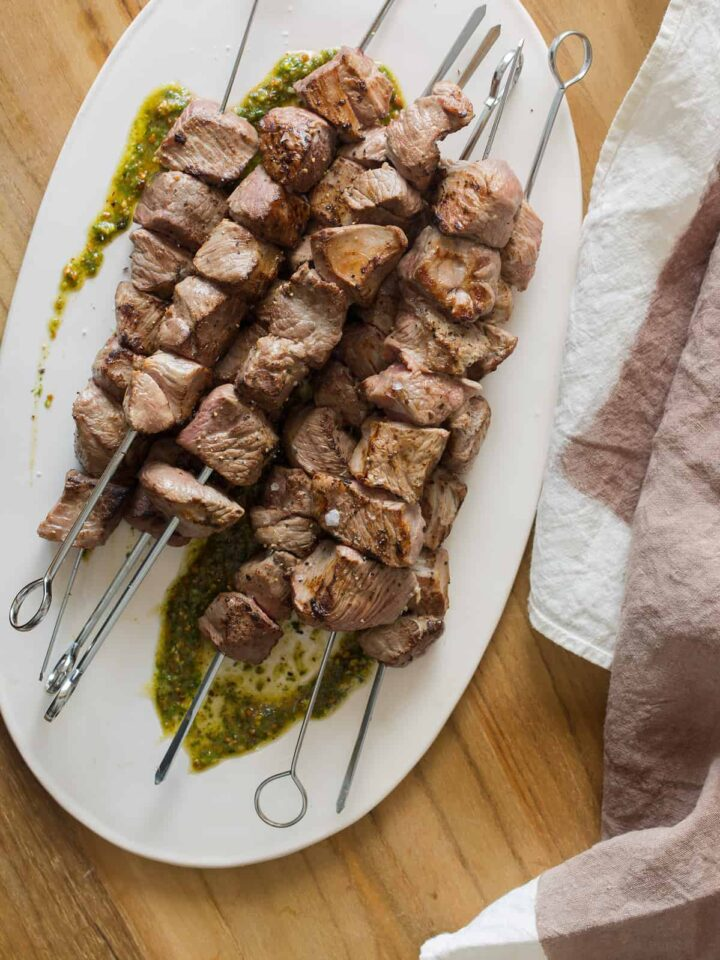 A plate of coconut milk marinated lamb kabobs with tarragon mint pesto and linens.