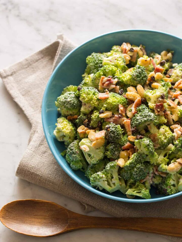 A bowl of broccoli crunch salad with a napkin and a wooden spoon.