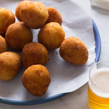 Coxinha on a blue plate with a drink.