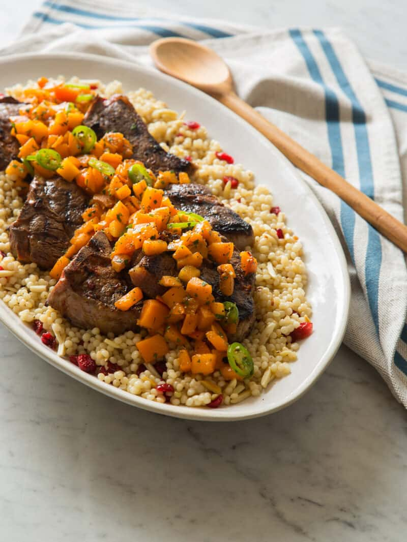 A platter of harissa grilled lamb chops with fresh apricot serrano salsa on couscous.