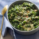 Creamed kale in a large serving dish with a spoon on a blue linen.
