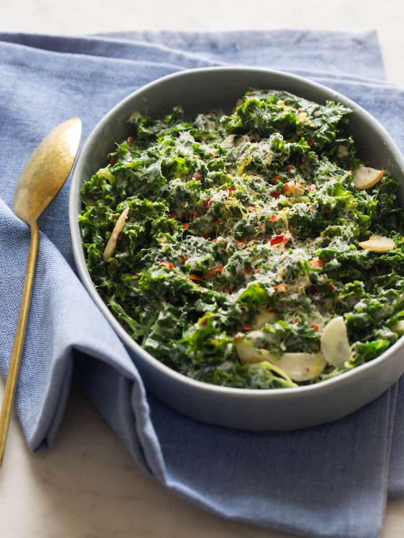 A serving dish of creamed kale with a blue napkin and a spoon.
