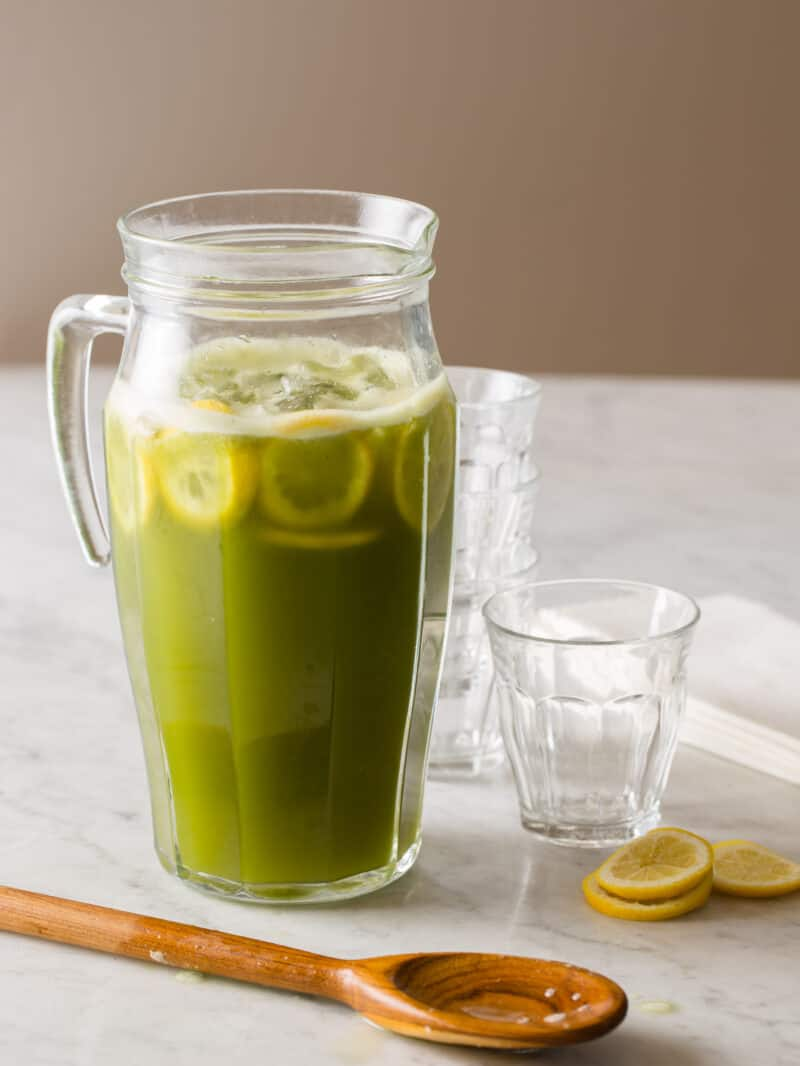 A glass pitcher of matcha lemonade with extra glasses and lemon slices.