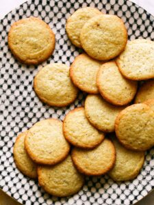 Pile of chewy lemon cookies on black and white plate.