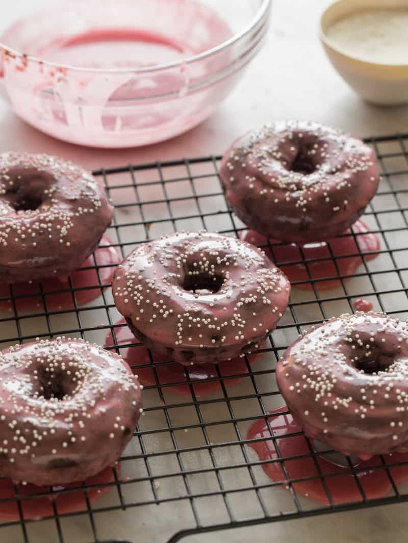 Chocolate baked donuts with a bowl of plum glaze in the background.