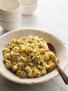 A bowl of creamy potato salad with a spoon and extra bowls.