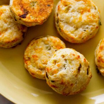 A close up of roasted hatch and cheddar biscuits on a yellow plate.